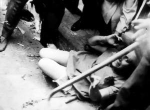 """Началото на юли 1941 г. Еврейка e просната на тротоара при погром в Лвов, устроен от щурмоваци на т.нар. """"Украинска народна милиция"""", зад която стои организацията ОУН (б)."""