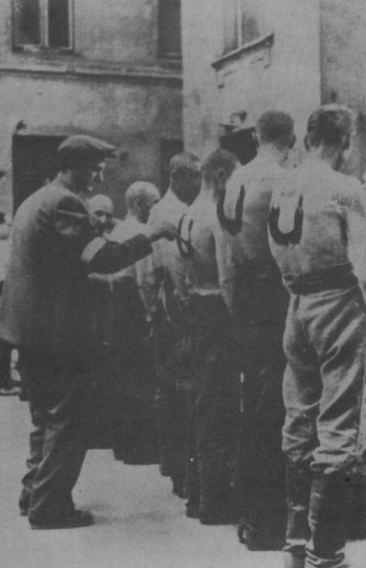 """Септември 1944 г. Жител на Варшава изписва буквата """"U"""" върху гърбовете на пленени украински колаборационисти, които взимат дейно участие в потушаването на полското въстание срещу нацистките окупатори."""